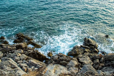 The sea view. Waves break about the coastal stones. Evening lighting Stock Photo