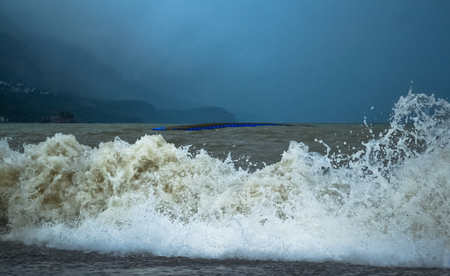 Sea wave in stormy weather. The turbid wave. Low clouds over the coast. Montenegrin beach in rainy weather. Montenegro.