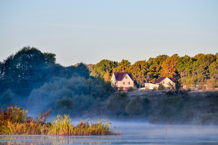 Idyllic secluded place for living in nature. Houses near a forest lake. Fog over the water. Autumn Stock Photo