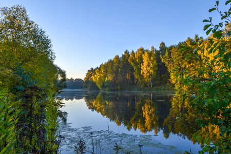 The autumn forest is reflected in the calm blue water of the forest lake. Early morning.
