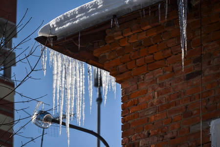 Brick wall of a residential building and large icicles. Icicles hang from the roof, vertically. an ice stalactite hanging from the roof. Dangerous icicles Stock Photo