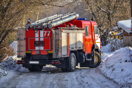 Russia. The red fire truck is moving to the fire in the yards. Winter. Snow.