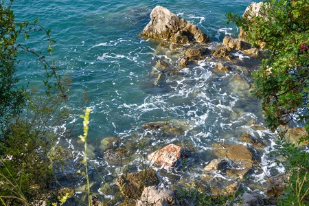 Huge stones in the sea and waves. On a sunny day. View from above. Montenegro. The Budva Riviera Stock Photo