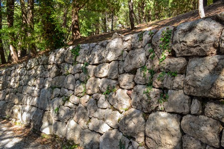An old stone wall made of rough stone. An ancient fortified wall fence with a pattern of green grass and moss.