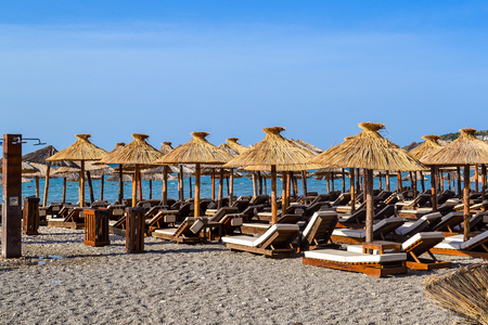 The beach with straw umbrellas from the sun and soft sun loungers. Adriatic coast. Summer. Without people.