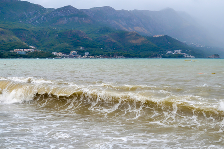 Sea wave in stormy weather. The turbid wave. Low clouds over the coast. Montenegrin beach in rainy weather. The sea and mountains of Montenegro. Budva. Becici 스톡 콘텐츠