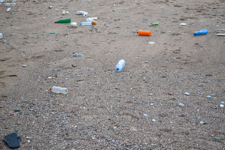 Garbage is carried by storm to the beach. Ecology. Pollution of the sea.
