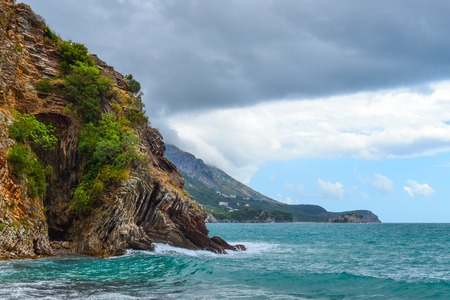 Beautiful view of the sea. The mountains descend into the sea. The sky with rain clouds, the waves foam. Adriatic Sea. Montenegro