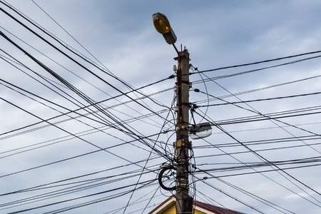 A lot of wires on the lamp post. A tangle of wires, a mess in electricity. Russia
