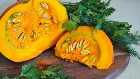 Orange fresh pumpkin, with greens. cut slices of pumpkin on the table