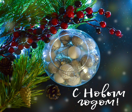 Beautiful Christmas decorations in a round glass. Spruce branches, light. And the inscription in Russian Happy New Year. Top view Imagens
