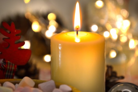 One candle burning brightly in the dark against a background of blurry lights. Romance, festive evening