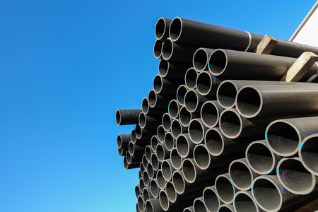 Plastic pipes in the assortment of finished products packed in packages against a blue sky