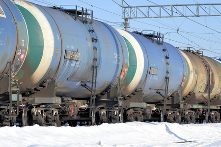Train. Cars for transportation of fuel. Winter is a sunny day. Russia Stock Photo