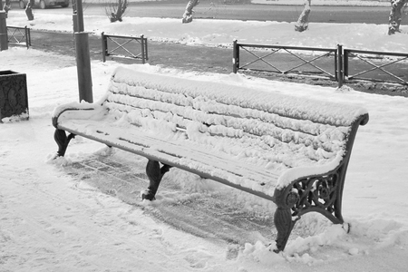 The bench is covered with snow and ice on a sunny winter day in the park. Monochrome. Stok Fotoğraf