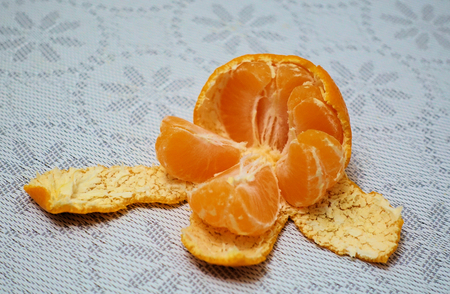 Peeled mandarin divided into slices on a white cloth 스톡 콘텐츠