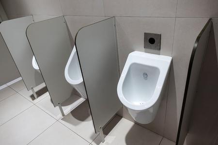 Closeup of three white urinals in mens bathroom design of white ceramic urinals for men in toilet room, Loft wall