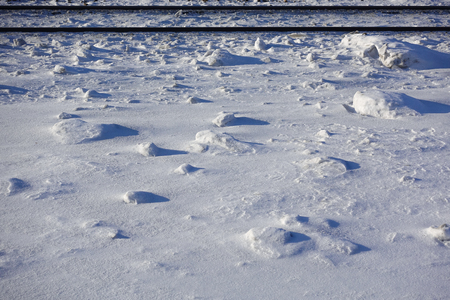 Field covered with snowballs. Lifeless landscape. Winter field on a sunny day. two parallel railway tracks. Winter background