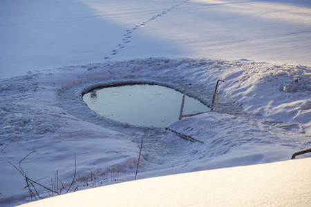 Ice hole in the lake in winter is equipped with a ladder for launching.