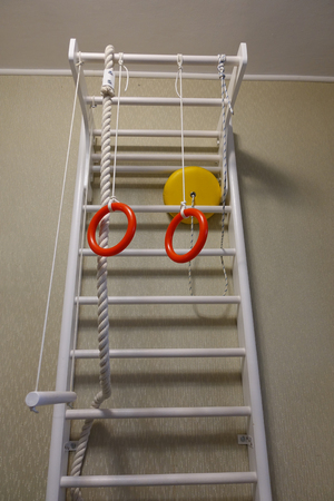 Children's sports complex. Baby sports wall. Ladders, sports rings Imagens
