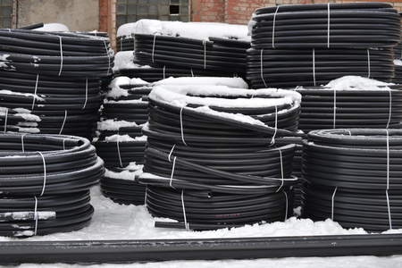 Plastic pipes in the finished goods warehouse are stacked in packs in the snow