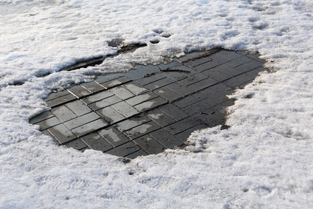 Closeup photograph of melting snow on a pavement made of gray concrete tiles.