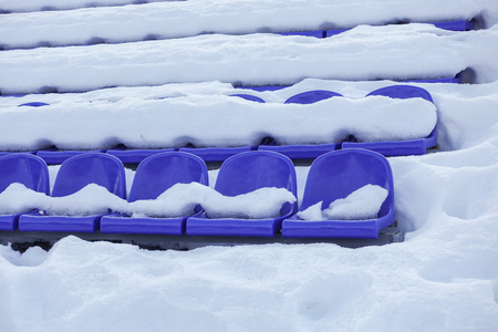 sports stadium bleachers in winter, chairs of the fans - empty seats of grandstands covered by snow