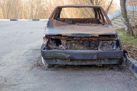 Abandoned burned passenger car near the apartment building. Russia. Archivio Fotografico