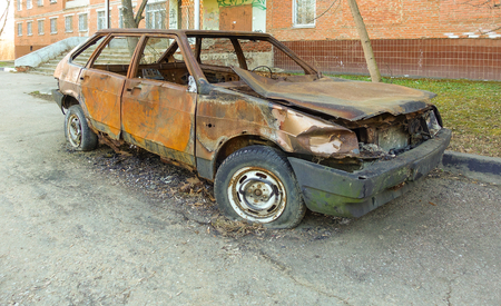 Abandoned burned passenger car near the apartment building. Russia. Stock Photo