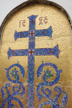 Mosaic image of the Orthodox cross with elements of vegetation. Blue cross on a golden background