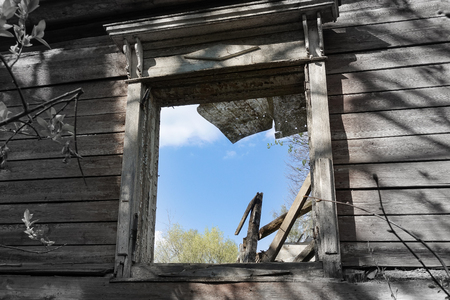 Window opening of an old ruined wooden house. Russia.