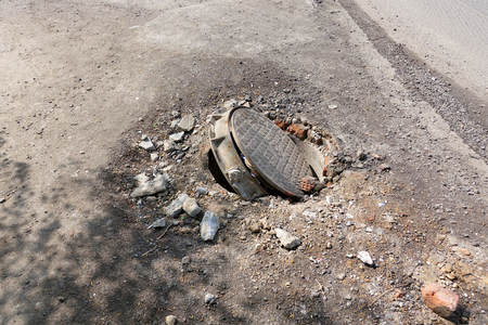 Broken sewer on the road. Danger of injury. Repair of communications