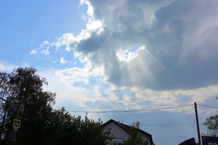 the suns rays pierce the clouds in the sky 写真素材