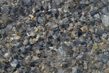 Top view of blue, green and turquoise colors of water, surface of sea on rocks and bottom. Reflection of sun beams in water, shallow soil, shoal of ocean. Sea texture, background, pattern, wallpaper.
