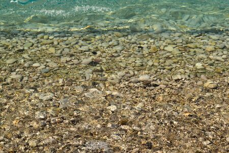 Sea stones in the sea water. Pebbles under water. The view from the top. Nautical background. Clean sea water. Transparent sea.