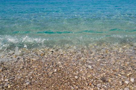 square background image of calm turquoise sea on shingle beach