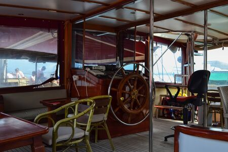 Steering wheel and engine controls on the ship bridge of a pleasure craft.