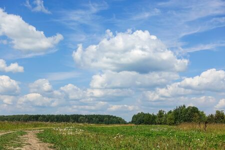 Country road and green grass and cloud sky. Russia Stock Photo