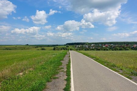 asphalt road through the green field and clouds on blue sky in summer day Stock Photo