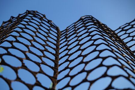Fencing of a metal sheet with round holes against the blue sky. Stock Photo