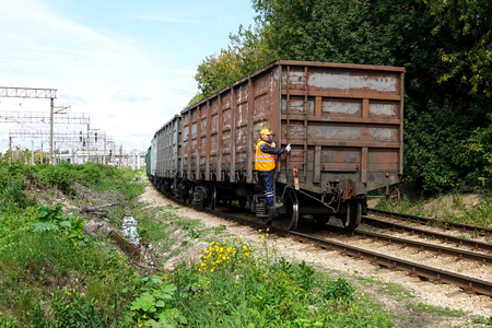 August 16, 2019 Russia, Podolsk. - The railway freight train makes a maneuver. Worker monitors movement