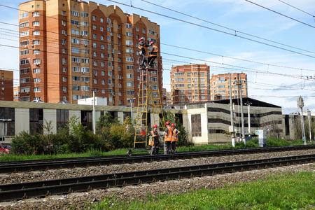 August 16, 2019 Russia, Podolsk. - Railway workers repair wires on the railway