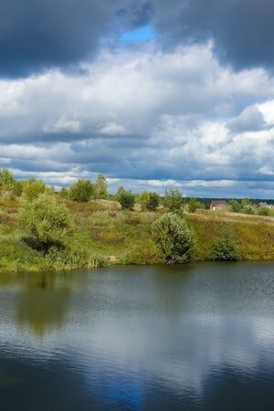 Beautiful rain clouds in the sky over the river and the steppe in the fall. Stock Photo