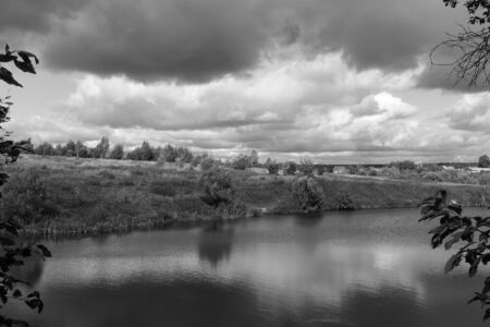 Beautiful rain clouds in the sky over the river and the steppe in the fall. Monochrome