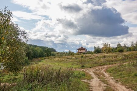Russian rural landscape in the fall, village houses near the forest. Sky with rain clouds