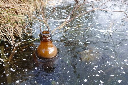 An empty glass bottle was frozen in the ice of the lake. Environmental pollution. Ecology.