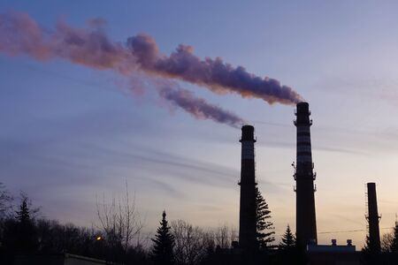 Steaming industrial chimneys at dawn. Winter frosty morning