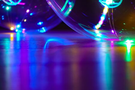 Colored lights reflect off a shiny surface at night. Bokeh Abstract holiday background Standard-Bild