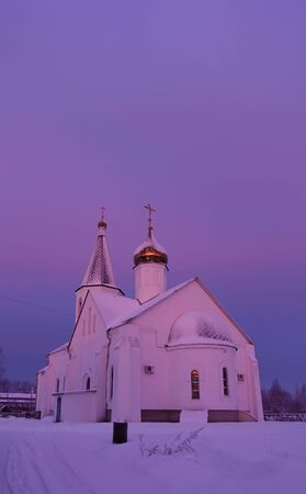 Winter frosty morning. The church is lit by pink and purple dawn colors. Russia Stok Fotoğraf