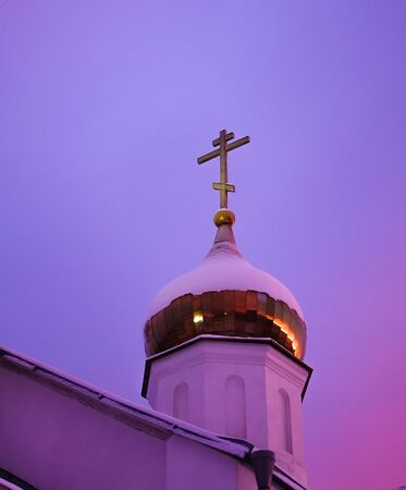 The dome of the church with a cross is lit by pink and purple flowers of dawn. Russia